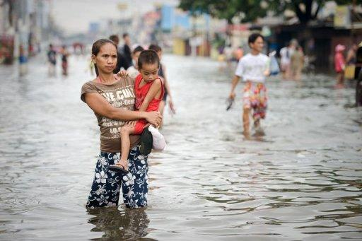 A woman holding a young boy wades through floodwaters in a street in the township of Apalit on the outskirts of Manila