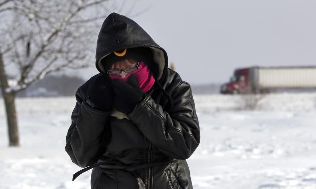 Megan Draper of Noblesville, Indiana covers her face to stay warm after stopping at a rest stop on Interstate 65 north of Indianapolis, Indiana January 6, 2014. A blast of Arctic air gripped the vast middle of the United States on Monday, bringing the coldest temperatures felt in two decades, causing at least four deaths, forcing businesses and schools to close and canceling thousands of flights. The polar vortex, the coldest air in the Northern hemisphere that hovers over the polar region in winter but can be pushed south, was moving toward the�East Coastwhere temperatures were expected to fall into Tuesday. REUTERS/Nate Chute (UNITED STATES - Tags: ENVIRONMENT TPX IMAGES OF THE DAY)