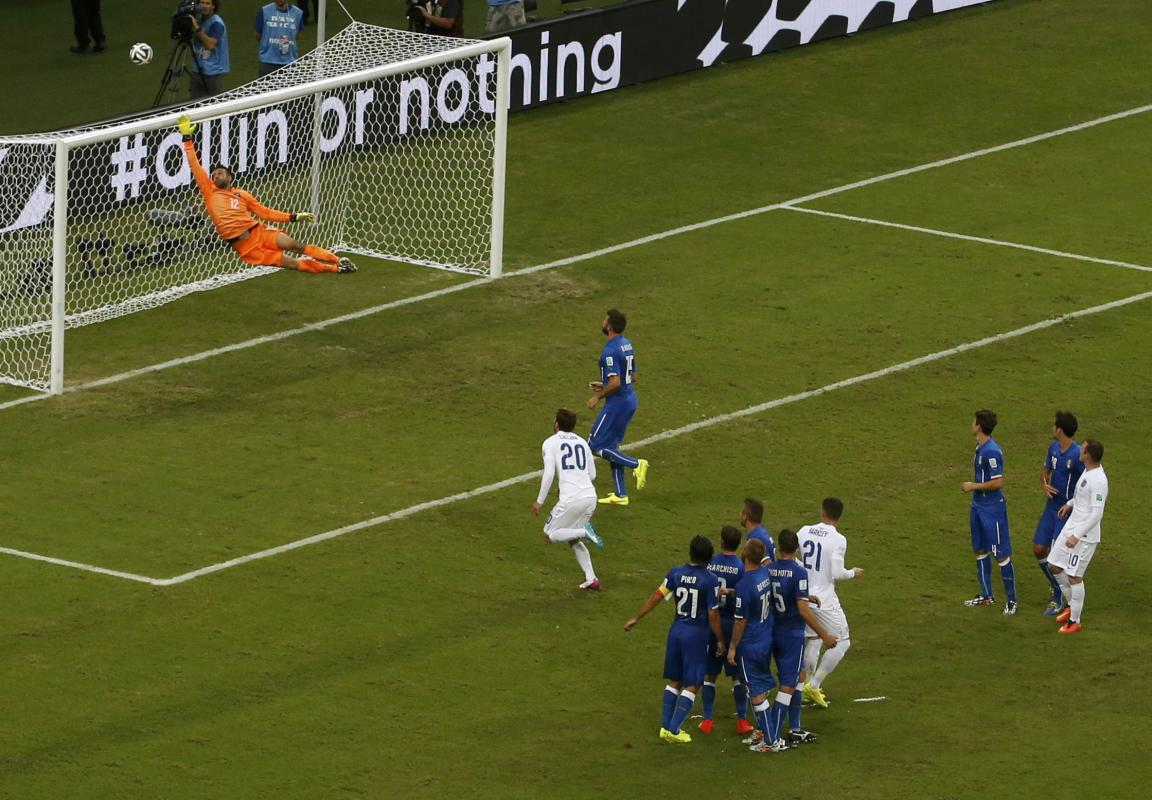 The ball sails over Italy's goalkeeper Sirigu after a free kick for England during their 2014 World Cup Group D soccer match at the Amazonia arena...