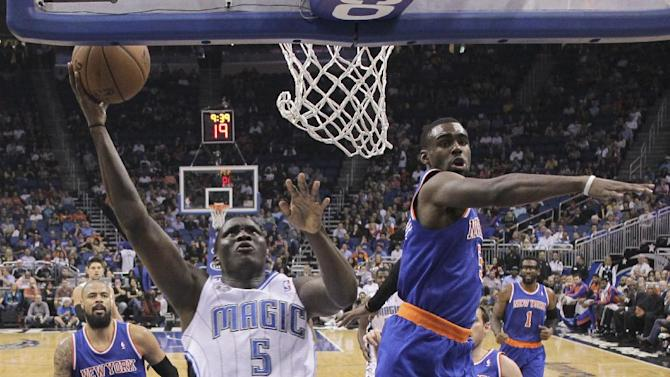 Orlando Magic's Victor Oladipo (5) shoots as he gets past New York Knicks' Tim Hardaway Jr., right, in the first half of an NBA basketball game in Orlando, Fla., Monday, Dec. 23, 2013