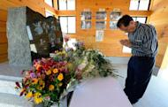 "A tourist prays for victims in front of a monument in Rikuzentakata, Japan, on July 20, 2013. Though the city was nearly wiped off the map by the 2011 tsunami, visitors are flocking back to see the devastation, the latest example of a phenomenon dubbed ""dark tourism"" where holidaymakers pay to witness the aftermath of others' misery"