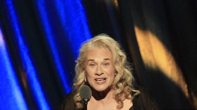 "FILE - In this April 14, 2012 file photo, singer Carole King introduces Don Kirshner for the Ahmet Ertegun Award at induction ceremonies for the Rock and Roll Hall of Fame in Cleveland.  King, now a best-selling author, doubts she will ever write another song and suggested that her 2010 ""Troubadours Reunion"" concert tour with James Taylor would be her last. She recently released a memoir called, ""A Natural Woman.""   (AP Photo/Tony Dejak, file)"