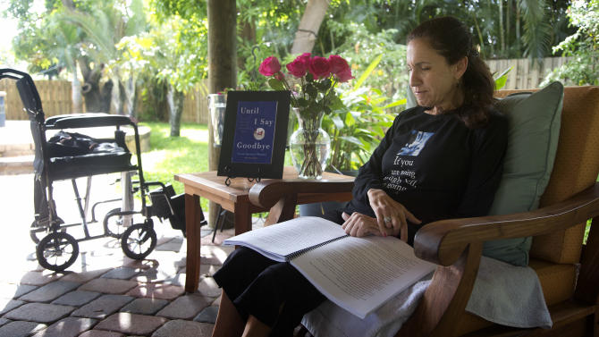 In this Dec. 31, 2012 photo, Susan Spencer-Wendel sits in her backyard at her home in West Palm Beach, Fla., reading a printed copy of her book. All the time-stamped rigors of daily journalism are behind her, but the pace of Spencer-Wendel's life has only been hastened. She is dying from Lou Gehrig's disease. What was once a constant rush to be first with her courthouse scoops has become a dash to live her remaining days joyfully, complete a long goodbye to those she loves, and record it all in a book that has drummed huge interest and a multimillion-dollar book deal. (AP Photo/J Pat Carter)