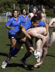EDS NOTE: NUDITY - Spanish Conquistadoras' Anna Paloma tackles Dunedin's Nude Blacks player during their friendly rugby match at Kettle Park in Dunedin, New Zealand, Saturday, Sept. 10, 2011, prior to the Rugby World Cup match between England and Argentina. (AP Photo/Natacha Pisarenko)
