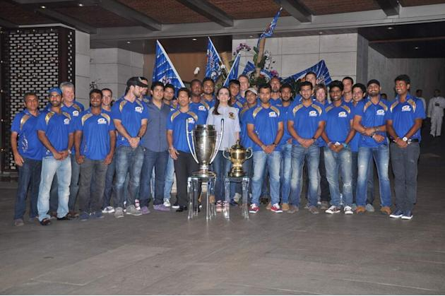 The Mumbai Indians squad poses with the CLT20 and IPL trophies