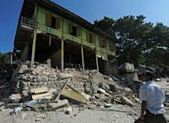 Maynmar villagers walk past an earthquake damaged house in Thabeik Kyin township, Mandalay. The quake has left 38 people dead or missing, the Red Cross said as a new tremor rattled the government's capital Naypyidaw