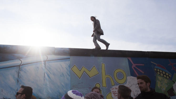 A man walks over the East Side Gallery named part of the former Berlin Wall during a protest against the removal of a section of the historic part of the former Wall, in Berlin, Sunday, March 17, 2013.  (AP Photo/Markus Schreiber)