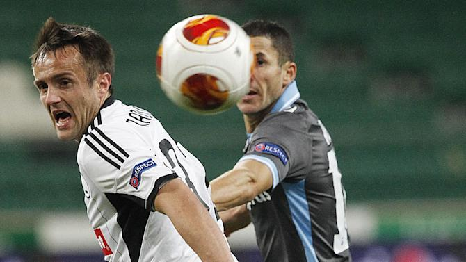 Calmel Meriem,right, of Apollon Limassol FC challenges for the ball with Miroslav Radovic, left, of Legia Warsaw, during their Europa League group J soccer match in Warsaw, Poland, Thursday, Oct. 3, 2013