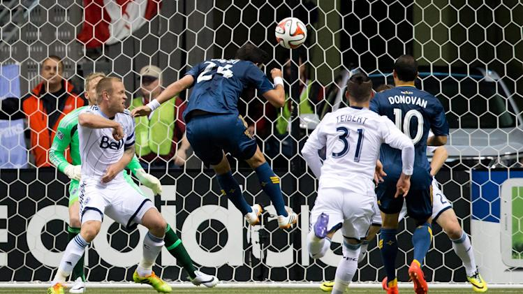 Los Angeles Galaxy's Stefan Ishizaki, of Sweden, (24) scores a goal as teammate Landon Donovan (10) and Vancouver Whitecaps' Jay DeMerit, left, and goalkeeper David Ousted, of Denmark, back left, watch during the first half of an MLS soccer game Saturday, April 19, 2014, in Vancouver, British Columbia
