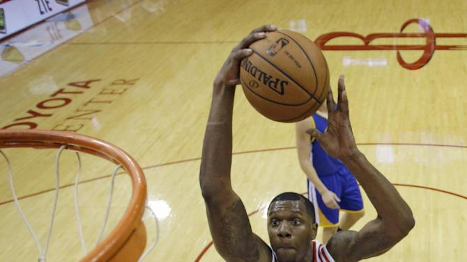 Houston Rockets' Terrence Jones (6) goes up for a shot over Dwight Howard (12) as Golden State Warriors' Harrison Barnes (40), left, defends during the first quarter of an NBA basketball game Friday, Dec. 6, 2013, in Houston