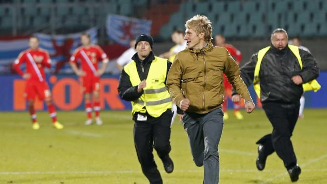 A supporter is chased by security guards as he runs on the pitch during the 2014 World Cup qualifying soccer match between Luxembourg and Russia in Luxembourg