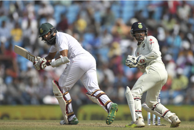 South African cricket team captain Hashim Amla, left, and Indian wicket-keeper Wriddhiman Saha look at the ball, on the third day of the third cricket test match between the two countries in Nagpur, I
