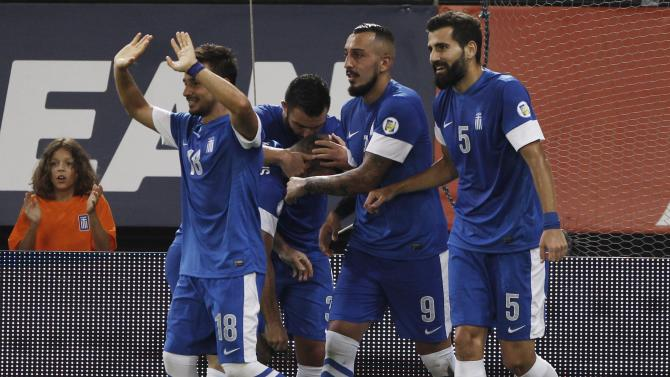 Greece's players celebrate after scoring against Latvia during their 2014 World Cup qualifying soccer match in Piraeus near Athens