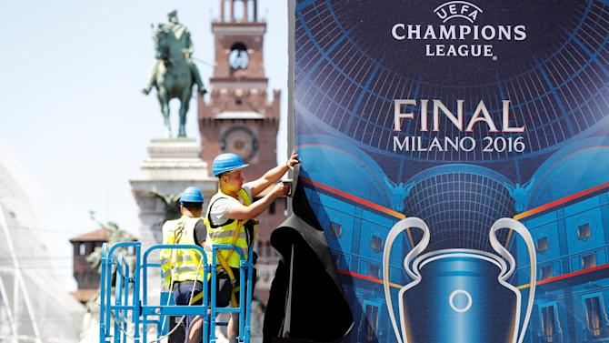 Workers set a banner of the UEFA Champions League Final 2016 downtown Milan