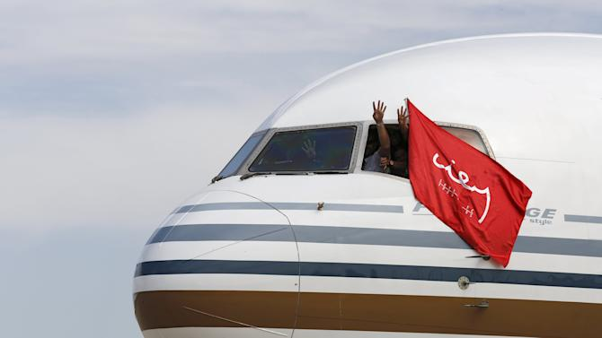 Crew of the flight of Sevilla's soccer team make the sign of four, the times Sevilla has won their Europa League trophy after landing in the Andalusian capital of Seville