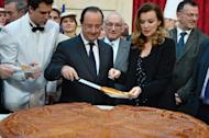 French President Francois Hollande (C) and his companion Valerie Trierweiler (2nd R) cut slices of a traditional epiphany cake at the Elysee Palace in Paris on January 7, 2014