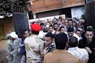 Egyptian voters scuffle with army soldiers as they enter a polling station in Giza, south of Cairo, on December 22, 2012. On the eve of Saturday's polling, clashes in Egypt's second city Alexandria left 62 people injured as stone-throwing mobs torched vehicles, underlining the turmoil gripping the Arab world's most populous nation