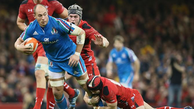 Wales's Dan Lydiate, center, goes to grab Italy's Sergio Parisse, second left, down as his teammate Leigh Halfpenny, below, tackles during their Six Nations international rugby union match between Wales and Italy at the Millennium stadium in Cardiff, Wales, Saturday, Feb. 1, 2014. (AP Photo/Alastair Grant)