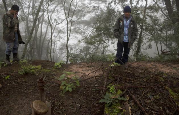 In this June 25, 2015 photo, Guarani environmental health specialist Albino Flores, right, and farmer David Benitez stand at the site of an unsealed oil well, left behind by the state-owned YPFB oil c