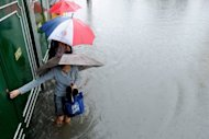 Pedestrians walk through floodwaters in Manila. Two people were killed by a collapsing wall as heavy rains pounded the Philippine capital Tuesday, bringing floods that have been worsened by garbage clogging the city's sewers and drains, officials said