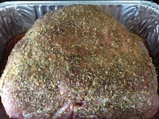 Pork shoulder rubbed with spices, ready to roast.