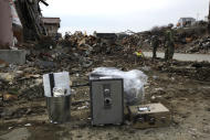 In this photo taken on April 7, 2011, Japan Self-Defense Force personnel stand near some safes they retrieved from houses destroyed by the tsunami in Ishinomaki, Miyagi Prefecture, northern Japan. Safes were washing up along the tsunami-battered coast, and police were trying to find their owners, a unique problem in the country where many people, especially the elderly, still stash their cash at home.