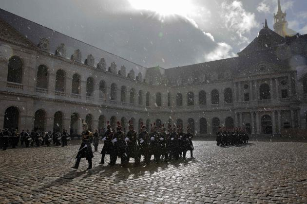 Republican Guards walk in the rain during a ceremony to welcome Quebec Premier Philippe Couillard in the courtyard of the Invalides in Paris