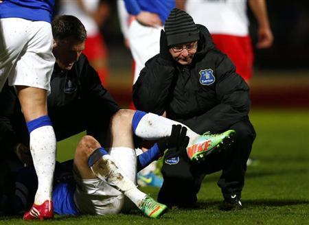 A physiotherapist holds the leg of Everton's Bryan Oviedo as he lies with a broken leg during their English FA Cup soccer match against Stevenage at Broadhall Way in Stevenage January 25, 2014. REUTERS/Eddie Keogh/Files