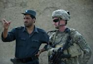 "A US soldier consults with a member of the Afghan National Police during a joint patrol in Kandahar province, September 12, 2012. NATO-led forces are scaling back joint operations with Afghan forces after a spate of ""insider attacks"" in which Afghan recruits turned their weapons on Western allies, officers said."