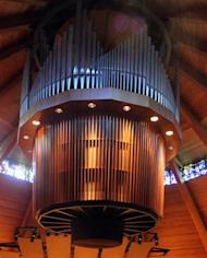 Organ pipes are suspended from the ceiling at the Agnes Flanagan Chapel Tuesday, June 12, 2012, on the campus of Lewis & Clark College, in Portland, Ore. The Agnes Flanagan Chapel is a 16-sided architectural marvel that seats 650 under stained glass windows depicting the book of Genesis. In the early 1970s, it was also a big, conical quandary. Chapels aren't really chapels unless they have an organ, and the newly-minted structure at Portland's Lewis & Clark College was in need. (AP Photo/Rick Bowmer)