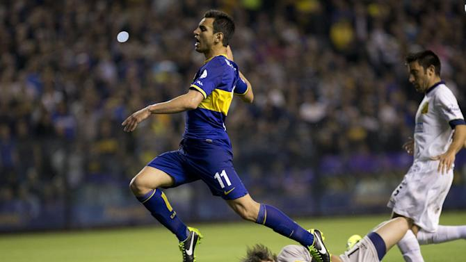 Boca Juniors' Juan Sanchez Mino leaps over Rosario Central's goalkeeper Mauricio Caranta during an Argentina's league soccer match in Buenos Aires, Argentina, Sunday, Oct. 13, 2013