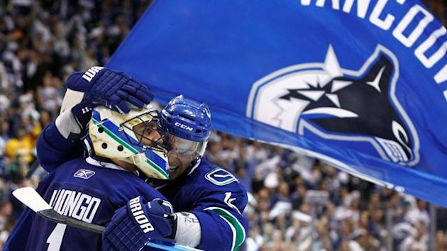 Vancouver Canucks goalie Roberto Luongo (L) and Alex Burrows celebrate after defeating the Boston Bruins in Game 5 of the NHL Stanley Cup hockey playoff in Vancouver, British Columbia June 10, 2011