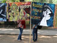 Demonstrators stand behind posters during a protest rally in New Delhi on February 21, 2013