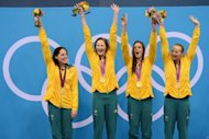 Australia's Alicia Coutts, Cate Campbell, Brittany Elmslie and Melanie Schlanger celebrate on the podium after winning the women's 4x100m freestyle relay swimming event at the London 2012 Olympic Games in London