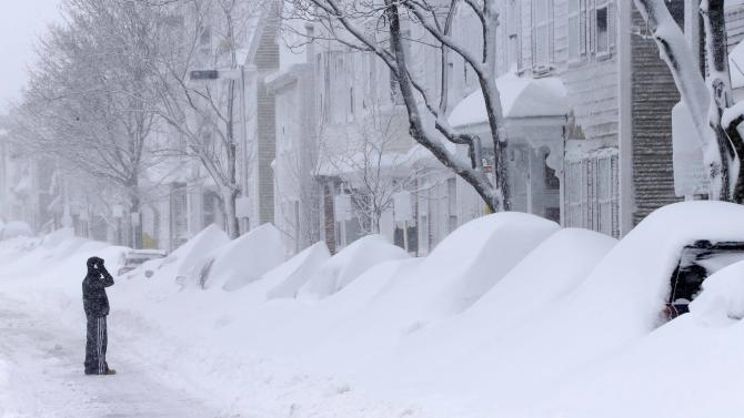 A man talks on the phone as he looks at a row of cars buried in snow on Third Street in the South Boston neighborhood of Boston Saturday, Feb. 9, 2013. (AP Photo/Gene J. Puskar)