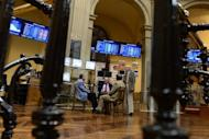 Traders talk next to the IBEX-35 index billboard at Madrid's stock exchange. Despite making progress, the eurozone debt crisis remains unsolved and, in a repeat of last summer, could still bring nasty surprises to global stock markets in July and August, analysts said