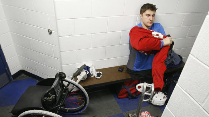 Brody Roybal, 15, prepares for an early morning workout on the ice on Tuesday, Feb. 11, 2014, in Bensenville, Ill. Roybal, who was born without legs, is the youngest member of the U.S. Paralympic sled hockey team which will be playing in Sochi, Russia in March 2014. (AP Photo/Martha Irvine)