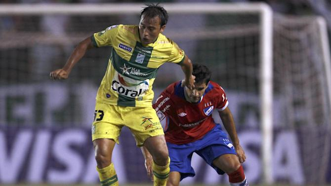 Wilder Zabala of Bolivia's Oriente Petrolero, left, fights for the ball with Juan Manuel Diaz of Uruguay's Nacional during a Copa Libertadores soccer match in Santa Cruz, Bolivia, Tuesday, Jan. 28, 2014