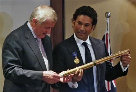 Cricket player Sachin Tendulkar (R) and Australia's Minister for the Arts and Regional Australia Simon Crean hold a cricket stump painted by an Australian aboriginal artist during a ceremony at a hote
