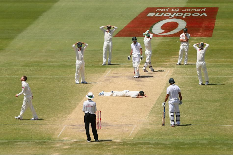 Australia fielder Rob Quiney lies on the pitch after missing a catch off South Africa's Faf du Plessis during day five of the Second Test Match between Australia and South Africa at Adelaide Oval on N