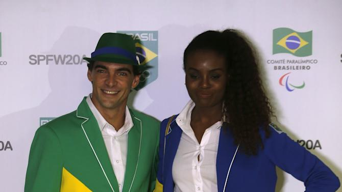 Brazil's Olympic volleyball medalists Giba and Fabiana pose with Brazil's uniform, that will be used by Brazilian athletes during the Toronto Pan American Games, in Sao Paulo