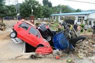 Chinese workers try to clear up damaged cars and debris after heavy rains in Beijing on July 23. The death toll from the worst rains to hit Beijing in more than 60 years has risen to 77 -- more than double the previous figure, according to the Xinhua news agency