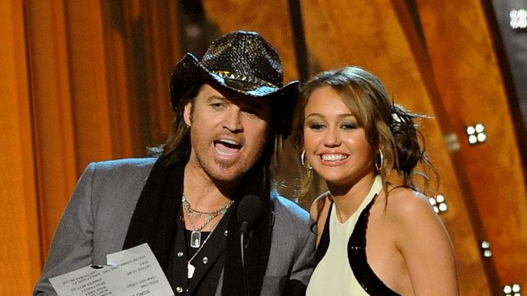 Presenters Billy Ray Cyrus and Miley Cyrus speak on stage during the 42nd Annual CMA Awards at the Sommet Center on November 12, 2008 in Nashville, Tennessee.
