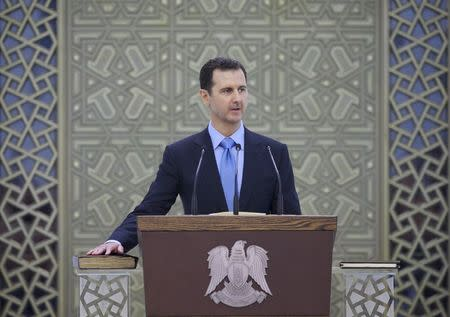 Syria's President Bashar al-Assad places his right hand on a Koran as he is sworn in for a new seven-year term, at al-Shaab presidential palace in Damascus July 16, 2014, in this picture released by Syria's national news agency SANA. REUTERS/SANA/Handout via Reuters