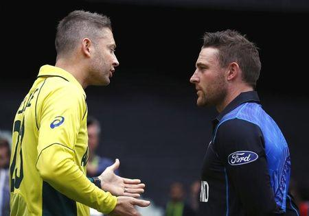 Australia's captain Michael Clarke talks with New Zealand captain Brendon McCullum after they posed with the Cricket World Cup trophy during a promotional event ahead of their final match at the M