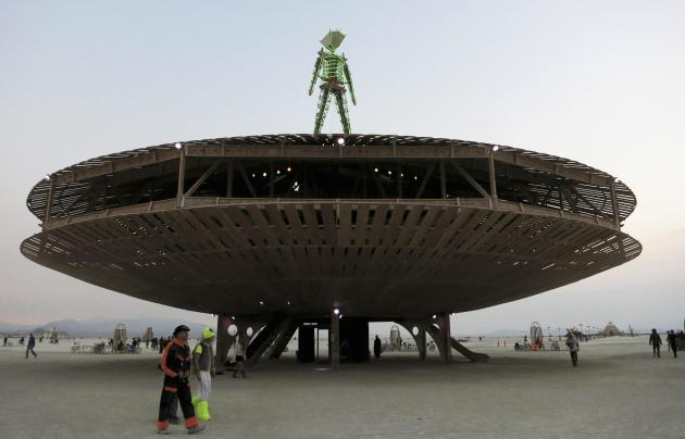 Participants walk past the effigy of the Man, seen at the center of the 2013 Burning Man arts and music festival in the Black Rock Desert of Nevada