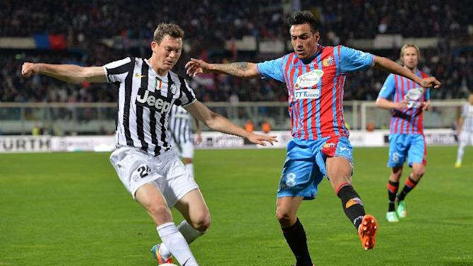 Juventus defender Stephan Lichtsteiner, left, of Switzerland, vies for the ball with Catania defender Fabian Monzon, of Argentina, during a Serie A soccer match at the Angelo Massimino stadium in Catania, Italy, Sunday, March 23, 2014