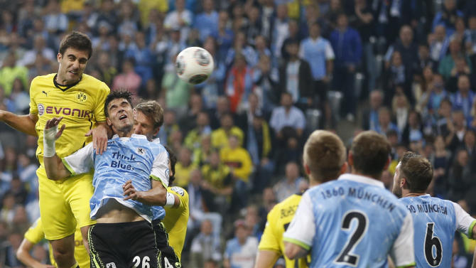 Munich's Christopher Schindler, 2nd left, and Dortmund's Nuri Sahin of Turkey challenge for the ball during the German soccer cup second round match between TSV 1860 Munich and Borussia Dortmund, in Munich, southern Germany, Tuesday, Sept. 24, 2013