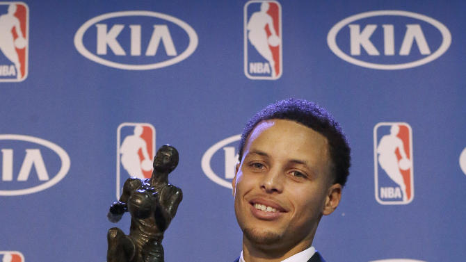 Golden State Warriors guard Stephen Curry holds the NBA's Most Valuable Player award at a basketball news conference Monday, May 4, 2015, in Oakland, Calif. Curry carried the top-seeded Warriors to a franchise-record 67 wins and surpassed his own record for most 3-pointers in a season. (AP Photo/Jeff Chiu)