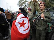 A woman wrapped in a Tunisian flag walks past a soldier standing guard during late opposition leader Chokri Belaid's funeral procession in Tunis, on February 8, 2013. Tunisian police have fired tear gas and clashed with protesters as tens of thousands joined the funeral of Belaid whose murder plunged the country into new post-revolt turmoil